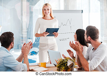 Great presentation! Cheerful young woman standing near...