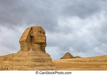 Great Sphinx profile wih pyramids on background in Giza,...