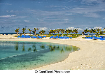 Beautiful bahamian beach with tropical plants of green palm trees blue clean atlantic ocean water and sandy coast in sunny summer weather in Great Stirrup Cay, Bahamas