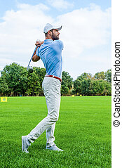 Great strike. Full length of confident golfer swinging his driver and looking away while standing on golf course