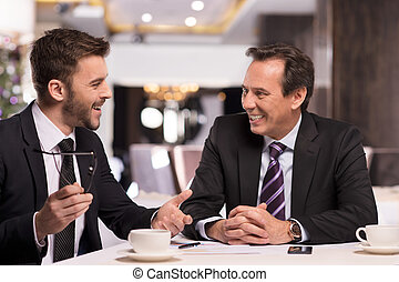 Great success. Two cheerful business people in formalwear discussing something and smiling while sitting at the restaurant