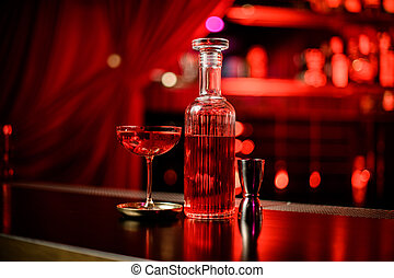 Great view of crystal bottle with liqueur and glass of cocktail on bar counter