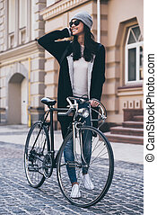 Great weather for a little ride. Beautiful young woman in sunglasses rolling her bicycle and looking away with smile while walking outdoors