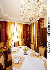 Greater chandelier above a greater dining table