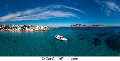Greece, Koufonisi island aerial drone panoramic view. Traditional wooden fishing boat moored, calm emerald sea water and blue sky background. Summer holidays and relaxation at small Cyclades