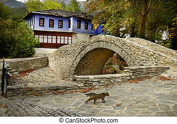 Greece, foot bridge and colourful home in mountain village...
