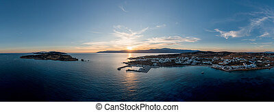 Greece, Koufonisia small Cyclades islands, aerial drone panoramic view at sunset. White traditional village buildings, sandy beach,  port and marina. Calm sea, blue sky background.