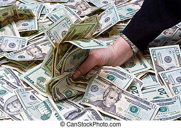 Greed - Womans hand grabbing money from a huge pile of...