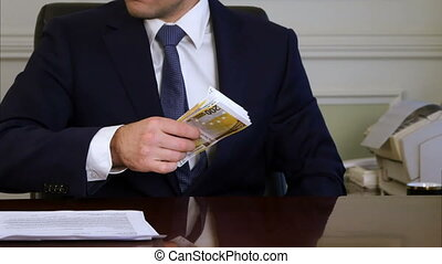 Greedy businessman takes euro packs out of money case