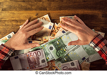 Greedy hands withdrawing pile of euro banknotes cash