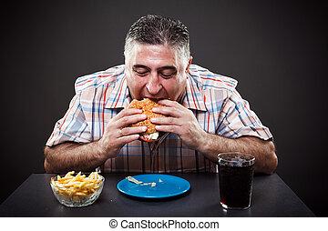 Greedy man eating burger - Portrait of a greedy fat man...