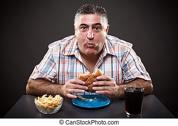 Greedy man eating burger - Portrait of a greedy man eating...