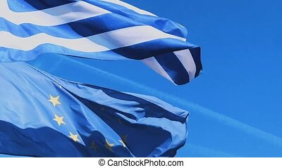 Greek and European Union flags and blue sky on a windy day, ...
