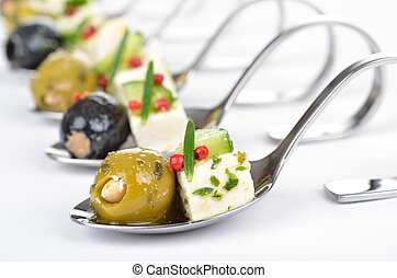 Greek appetizers on spoon - Stuffed (with almonds) green and...