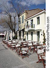 Greek cafe - Two historical buildings with chairs and tables...