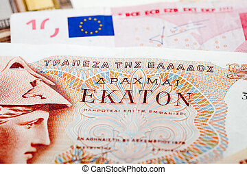Bank note of the former Greek currency Drachma on a background of Euro bank notes. As Greece has financial problems, a return to the former currency is considered.