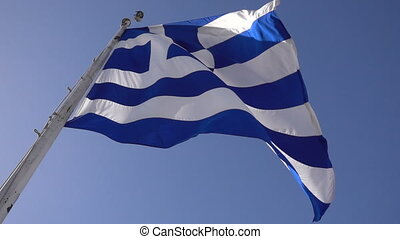 Greek flag waving against the blue sky, slow motion