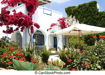 whitewashed greek island antiparos architecture hotel with arches and blue shutters and rails common to the greece cyclades islands with beautiful spring flowers