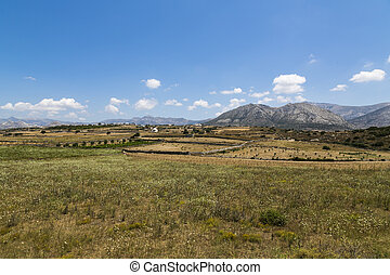 greek landscape with meadow, mountain and blue sky