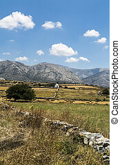 greek landscape with meadow, mountain and blue sky, white chapel in background .