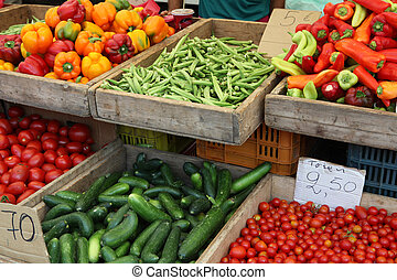 Vegetables on sale at a greek market stall - okra, cucumber, cherry tomatoes, plum tomatoes, capsicums and peppers,