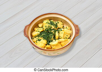 Greek potato salad with dill in a bowl on a white wooden table