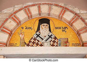 Greek priest in mosaic at the church wall