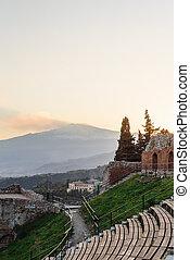 Greek reatre in Taormina Sicily, Italy, and Etna volcano in...