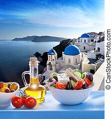 Greek salad against church in Oia village, Santorini island...