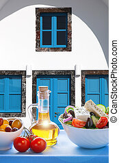Greek salad against old greek house, Santorini island, Greece