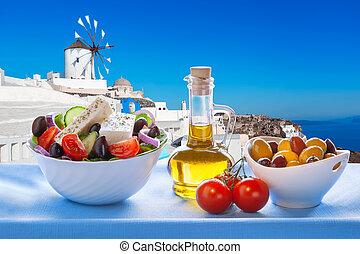 Greek salad against windmill in Oia village, Santorini ...