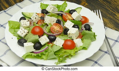 Greek salad with fresh vegetables, feta cheese and black...
