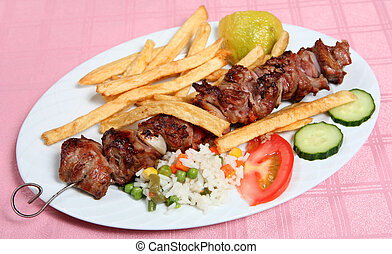 A lamb souvlaki, or kebab, on the skewer, served with french fried potato chips, rice and vegetables at a taverna.