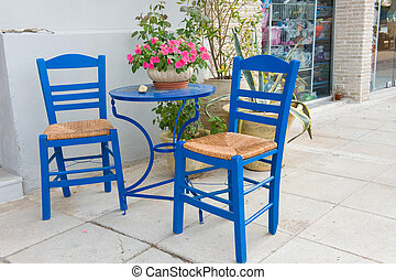 Greek terrace with blue chairs and table