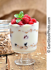 Greek yoghurt with oatmeal and fresh raspberries in a glass and mint leaves - vertical photo