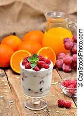 Greek yoghurt with oatmeal and fresh raspberries in a glass, mint leaves, orange juice, grapes in background - vertical photo