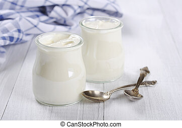 Greek yogurt in a glass jars with spoons on wooden...