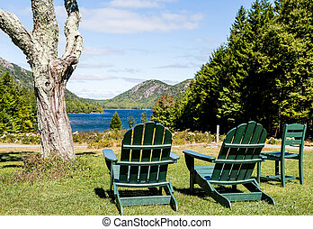 Green Adirondack Chairs Overlooking Lake - Two green...