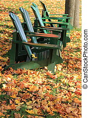 Green adirondack chairs with leaves
