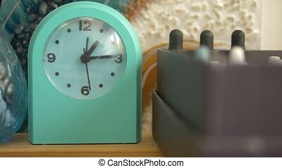 green alarm clock on a shelf in the artist's creative studio...