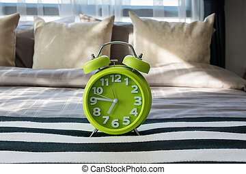 green alarm clock on bed in modern bedroom