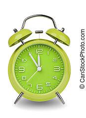 Green alarm clock with hands at 5 minutes till 12