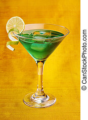 green alcohol cocktail with lime isolated on yellow background