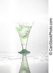 Green alcohol cocktail with splash isolated on white.