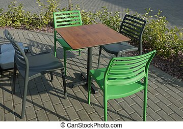 green and black plastic chairs by the brown table