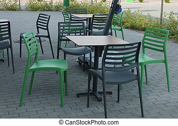 green and black plastic chairs by the table