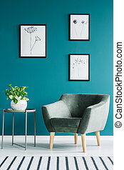 Green armchair next to table with plant against blue wall with posters in minimal living room interior