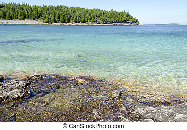 Green and blue water of Huron Lake, Ontario under blue sky.