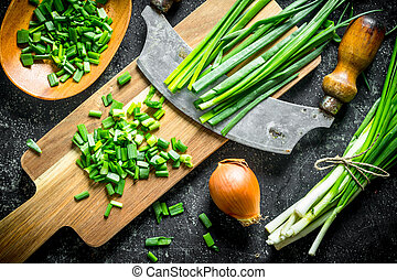 Green and onions with a large knife.
