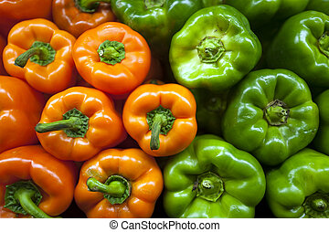Orange and greed peppers bunched together in market stand